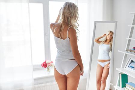 Foto de woman in underwear looking at mirror in morning - Imagen libre de derechos