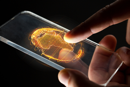 Foto de hands with smartphone and earth hologram - Imagen libre de derechos