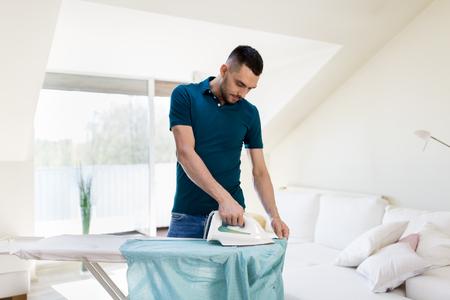 man ironing shirt by iron at home