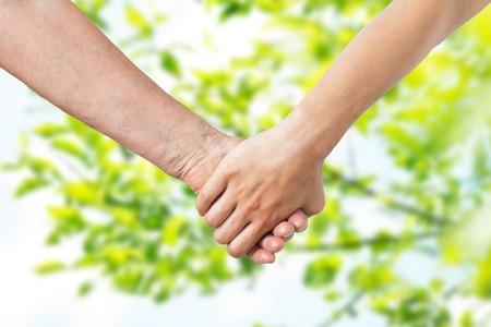 Photo pour close up of senior and young woman holding hands - image libre de droit