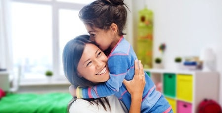 Photo pour family, motherhood and people concept - happy mother and daughter hugging and kissing over kids room at home background - image libre de droit
