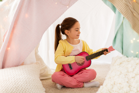 childhood and hygge concept - happy little girl playing toy guitar in kids tent at homeの写真素材