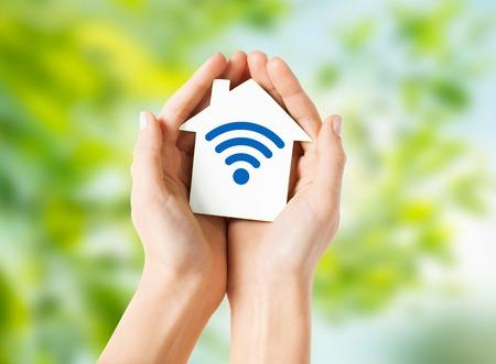 Photo pour hands holding house with radio wave signal icon - image libre de droit