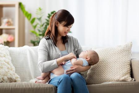 Foto de happy asian mother holding sleeping baby boy - Imagen libre de derechos