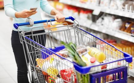 Foto de woman with smartphone buying food at supermarket - Imagen libre de derechos