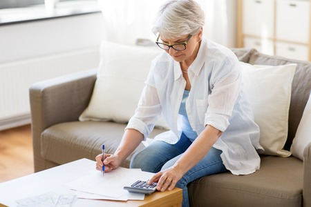 Foto de senior woman with papers and calculator at home - Imagen libre de derechos