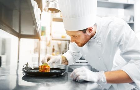 Photo pour happy male chef cooking food at restaurant kitchen - image libre de droit