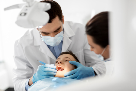 Photo for dentist checking for kid teeth at dental clinic - Royalty Free Image