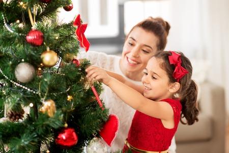 Photo pour happy family decorating christmas tree at home - image libre de droit