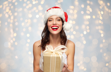 Photo for woman in santa hat with christmas gift - Royalty Free Image