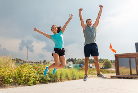 Photo for happy couple in sports clothes jumping on beach - Royalty Free Image
