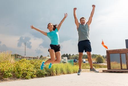 Foto für happy couple in sports clothes jumping on beach - Lizenzfreies Bild