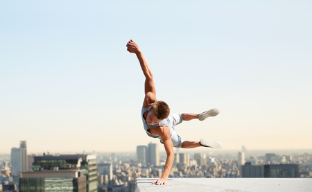 Foto de extreme sport, parkour and people concept - young man jumping high over tokyo city background - Imagen libre de derechos