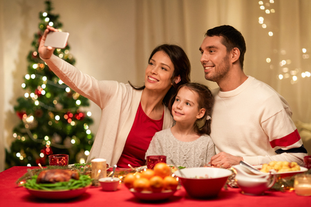 Photo pour holidays, family and celebration concept - happy mother, father and little daughter having christmas dinner and taking selfie picture by smartphone at home - image libre de droit