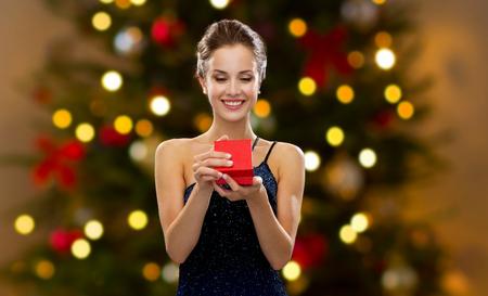Foto de woman with red gift box over christmas tree lights - Imagen libre de derechos