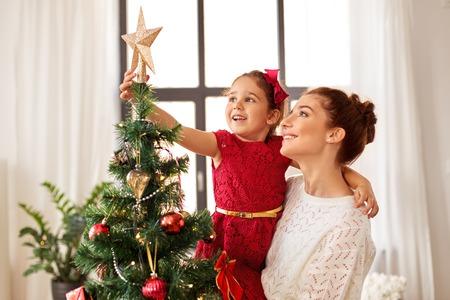 Photo pour mother and daughter decorating christmas tree - image libre de droit