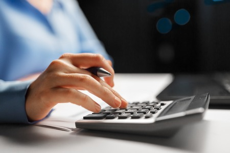 Foto de businesswoman with calculator at night office - Imagen libre de derechos