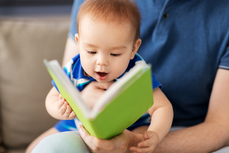 Foto de close up of baby boy and father with book at home - Imagen libre de derechos
