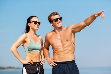Foto de happy couple in sports clothes and shades on beach - Imagen libre de derechos