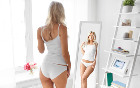 Photo pour woman in underwear looking at mirror in morning - image libre de droit
