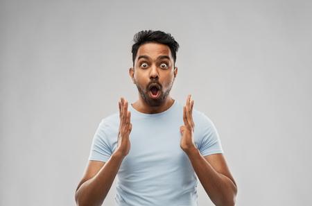 Foto de emotion, expression and people concept - scared man in t-shirt over grey background - Imagen libre de derechos