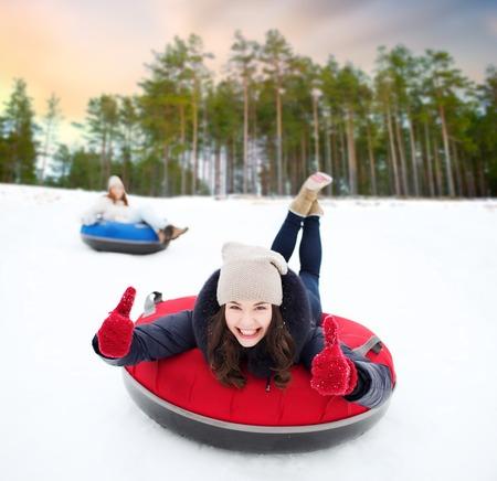 Photo pour happy teenage girl sliding down hill on snow tube - image libre de droit