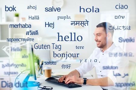 Foto de man with computer over words in foreign languages - Imagen libre de derechos