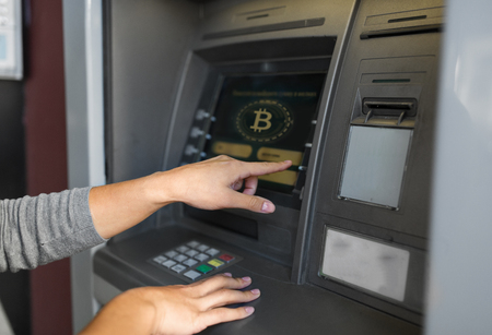 Photo pour woman at atm machine with bitcoin icon on screen - image libre de droit