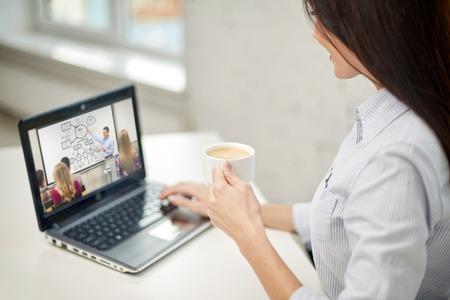Foto de woman with coffee watching webinar on laptop - Imagen libre de derechos