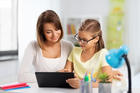 Photo pour mother and daughter with tablet pc doing homework - image libre de droit