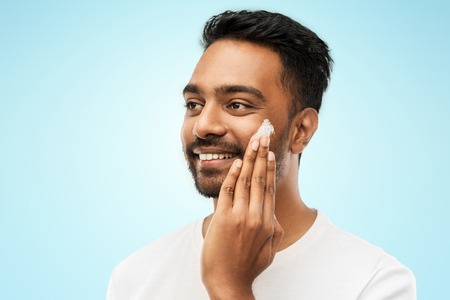 Photo pour happy indian man applying cream to face - image libre de droit