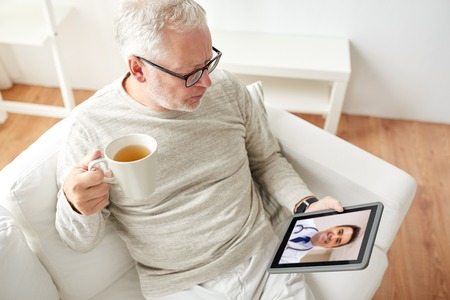 Photo pour senior man having video call with doctor on tablet - image libre de droit