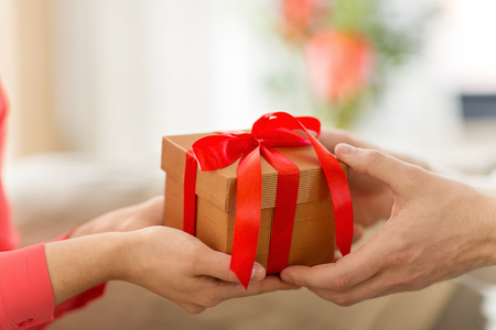 Photo pour close up of male and female hands with gift box - image libre de droit