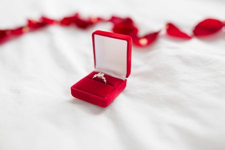 Foto de diamond ring in red velvet gift box on bed sheet - Imagen libre de derechos