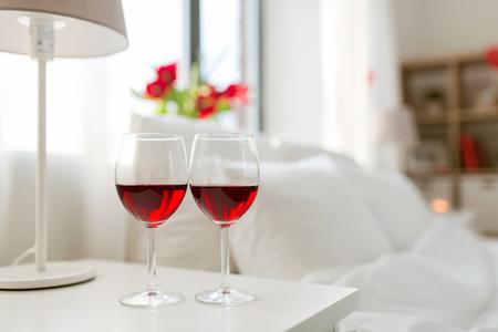 Foto de two glasses of wine on bedroom nightstand at home - Imagen libre de derechos