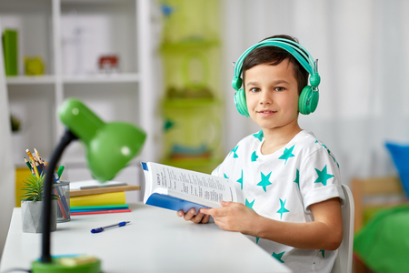 Photo pour boy in headphones with textbook learning at home - image libre de droit
