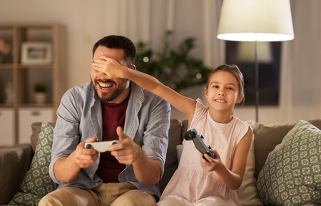 Foto de father and daughter playing video game at home - Imagen libre de derechos