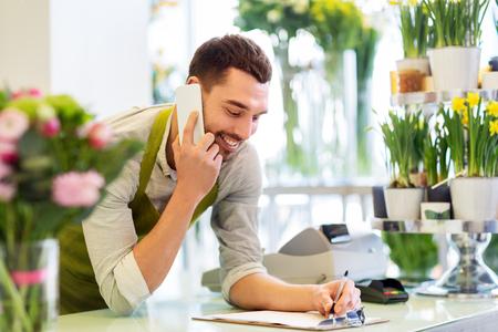 Photo pour florist man calling on smartphone at flower shop - image libre de droit