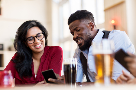 Foto de happy man and woman with smartphones at bar - Imagen libre de derechos
