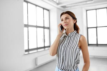 Foto de Businesswoman calling on smartphone at office - Imagen libre de derechos