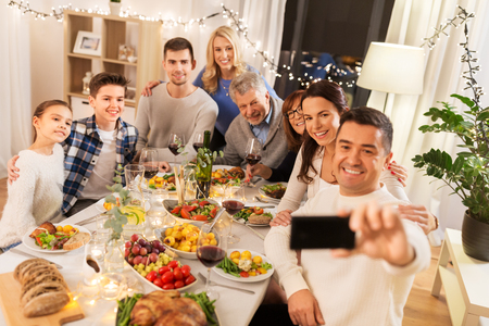 Foto de Happy family having dinner party and taking selfie - Imagen libre de derechos