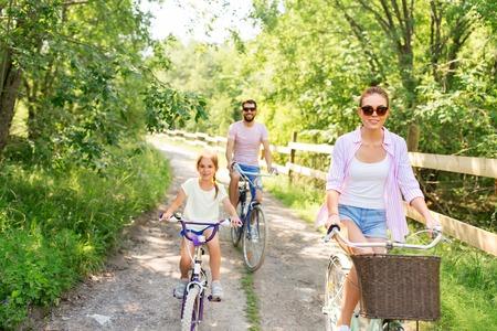 Foto de happy family with bicycles in summer park - Imagen libre de derechos