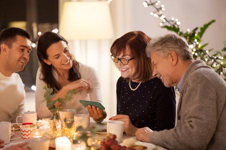 Foto de happy family with smartphone at tea party at home - Imagen libre de derechos
