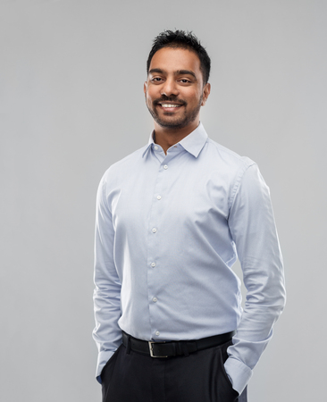 indian businessman in shirt over grey background