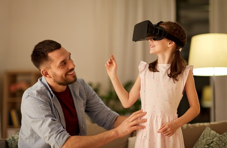 Photo pour father and daughter in vr glasses playing at home - image libre de droit