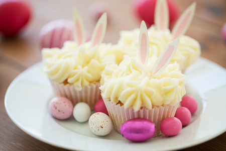 Photo for cupcakes with easter eggs and candies on plate - Royalty Free Image