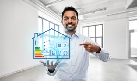 Photo pour automation, internet of things and technology concept - smiling indian businessman or realtor with smart home virtual projection over empty office room background - image libre de droit