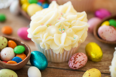 Photo for easter, food and sweets concept - frosted cupcakes with chocolate eggs and candies on table - Royalty Free Image