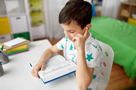 Foto de student boy in earphones reading book at home - Imagen libre de derechos