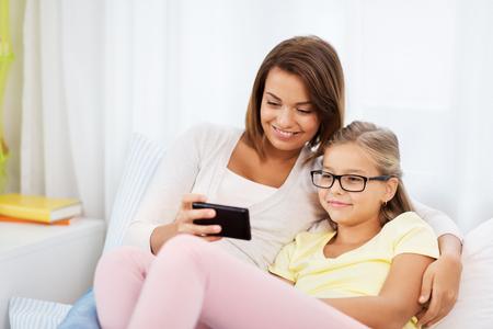 Foto de happy mother and daughter with smartphone at home - Imagen libre de derechos